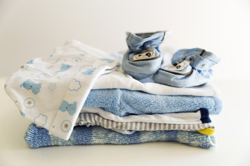 Set of things for a newborn baby boy. Maternal concept. Baby clothes in pile and tiny baby shoes and hat