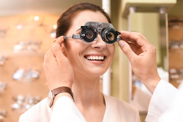 Woman having eye examination with phoropter in optical store. Ophthalmologist prescription