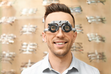 Young man having eye examination with phoropter in optical store. Ophthalmologist prescription