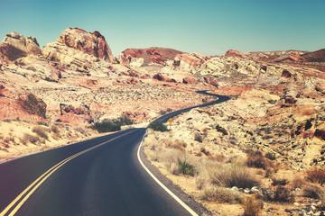Retro toned picture of a scenic winding road, travel concept, Nevada, USA.