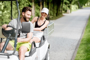 Young and happy couple having fun driving a golf cart during the summer sport activity
