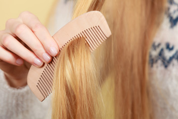 Blonde woman brushing her hair with comb