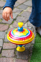 Vintage toy top spinning near a children