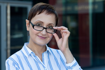 Business woman portrait. Professional headshot of middle aged businesswoman principal teacher wearing glasses and white shirt.