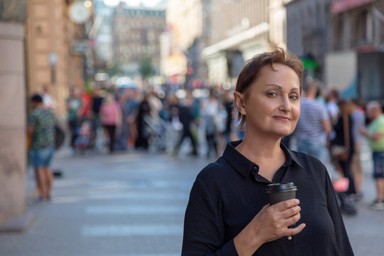 Nice portrait of a middle aged older woman walking in city. Outdoor headshot of 45 50 year old relaxed woman on lunch break drinking coffee. Urban background. Street style shot.