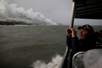 A spectator aboard a tour boat takes photos of the lava hitting the ocean during the eruption of the Kilauea Volcano near Pahoa, Hawaii