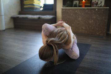 A young woman practicing Ashtanga yoga.