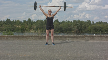 Female athlete doing crossfit deadlifts outdoors
