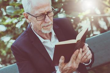 Man reading a book outdoors, light effect