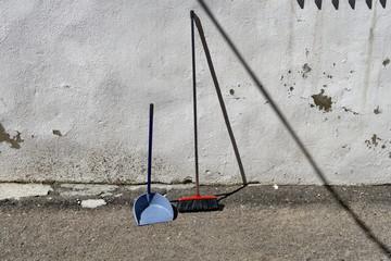 Balai et balayette appuyés sur un mur blanc