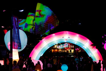 Crowds walk near an illuminated rainbow sculpture as projections on the sails of the Sydney Opera House are seen in the background during the official start of Vivid Sydney, promoted as the world's largest festival of light, music and ideas, in Sydney
