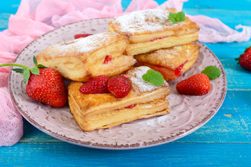 Sweet tasty puff pastry dessert on plate on wooden background. Delicious homemade cookies with strawberry jam, berries and sugar powder.
