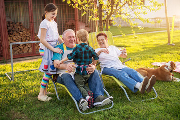 Elderly man is holding his little toddler grandson while his granddaughter is standing behind him and his wife sitting beside him on a beautiful day.