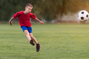 Boy kicking football on the sports field