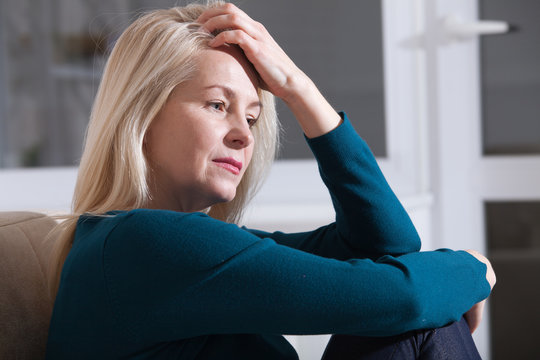 Sad depressed middle aged woman at home sitting on the couch, looking down and touching her forehead, loneliness and pain concept