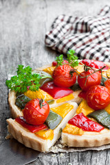 Vegetarian  quiche with colored pepper and cherry tomatoes on wooden table