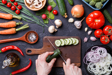 Photo on top of fresh vegetables, mushrooms, cutting board, oil, knife, hands of cook