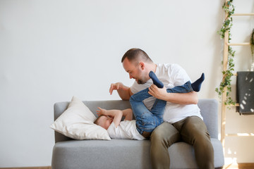 Image of young father with son playing on sofa