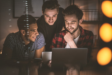 Group of excited friends investing money in electronic cryptocurrency on the Internet