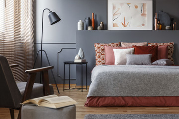 Close-up a book on a stool next to an armchair in a bedroom interior with a comfy bed with pillows, painting and lamp