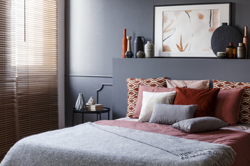 Pillows on a double bed next to a bedside table, decorations and painting above in a bedroom interior