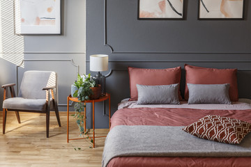 Cozy hotel room interior with a double bed with pillows next to a bedside table, plant and armchair