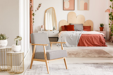 Patterned wooden armchair next to gold table in orange bedroom interior with bed. Real photo