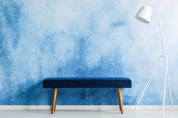 Blue bench and white lamp set on aquarelle wall in a waiting room interior. Place your product