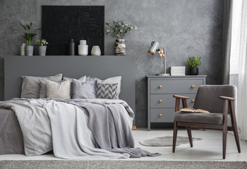 Grey armchair next to bed with pillows in dark bedroom interior with black poster. Real photo