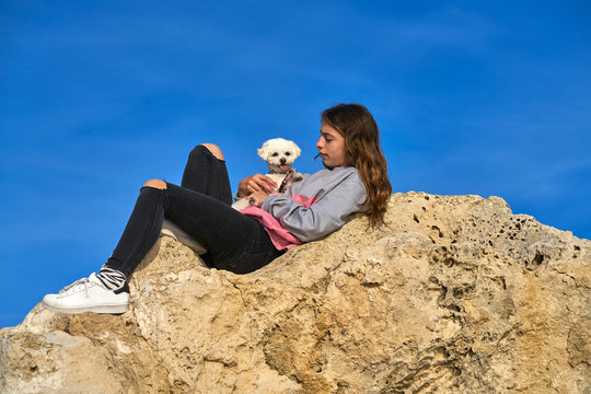 Girl playing with maltichon puppy dog on a rock
