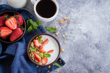 Organic Healthy Breakfast Food. Cup of coffee and Granola with greek yogurt and strawberry on gray concrete table background. Top view with copy space