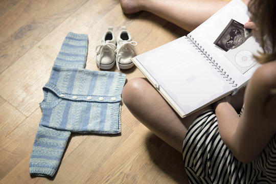 Woman placing baby's sonogram into baby's first year memory book. Baby clothes and sneakers laying on the floor