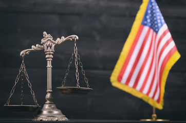 Scales of Justice in front of the American flag in the background.