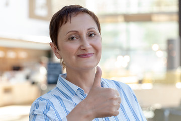 Woman giving  thumbs up, the thumb sign of approval