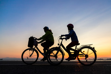 Silhouettes of people enjoying a walk by bicycle the seaside of the town during sunset