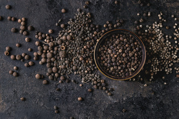 Canvas Prints Spices Variety of different black peppers allspice, pimento, monks pepper, peppercorns and ground powder in tin can over old black iron texture background. Top view, space.