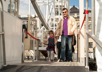 A smiling father with his daughter of four years go out holding hands, after riding a ferris wheel. Concept - happy childhood, happy fatherhood.