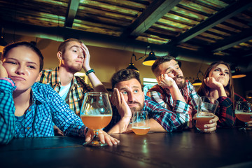 Upset male and female friends watching sport game or football match and drinking beer at bar or pub.