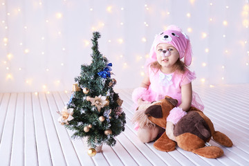 Little girl. Fir new year tree, bokeh. Dog costume