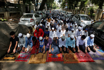 Men offer prayers on a street on the second Friday of the holy fasting month of Ramadan in Mumbai