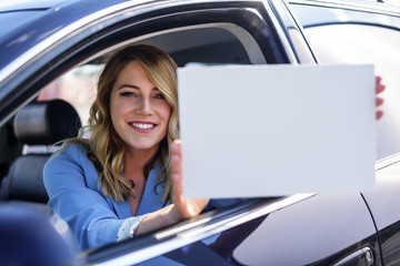 Woman sitting in the car and holding a white blank poster.