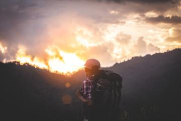 traveler man backpack enjoying sunset on mountain and looking sunlight.
