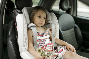 Portrait of little girl sitting in child's seat waiting