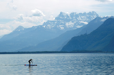 Man paddles on Lake Leman in front of the Dents-du-Midi mountains in Vevey