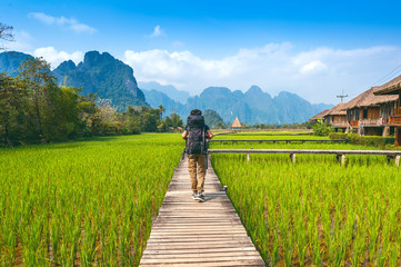 Tourism with backpack walking on wooden path, Vang vieng in Laos. Wall mural