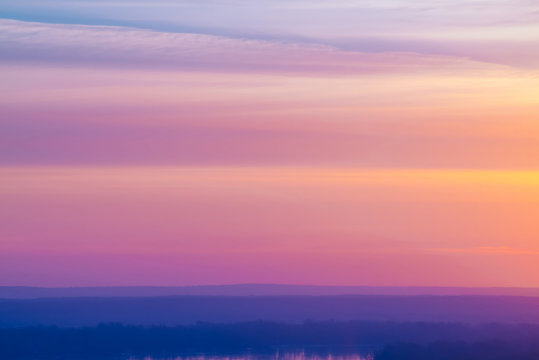 Varicolored striped surreal sky with shades of blue, cyan, pink, purple, magenta colors with cobalt land and lake. Horizontal lines of smooth clouds. Atmospheric image of tender sky, land and river.