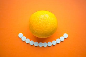 Summer vitamins. orange fruit and round white tablets as smile.Colorful of citrus fruit orange, lime,lemon, with vitamin c tablets on orange background