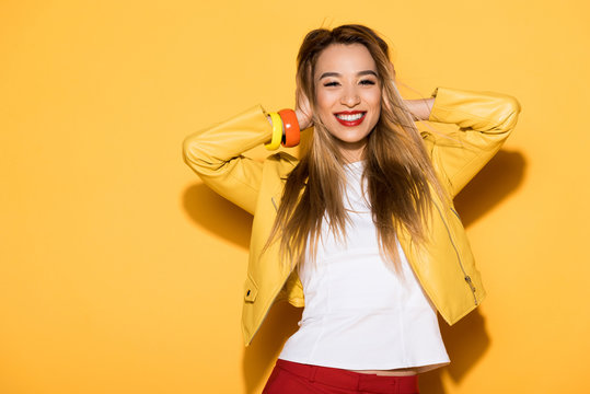 smiling asian female model closing ears by hands on yellow background