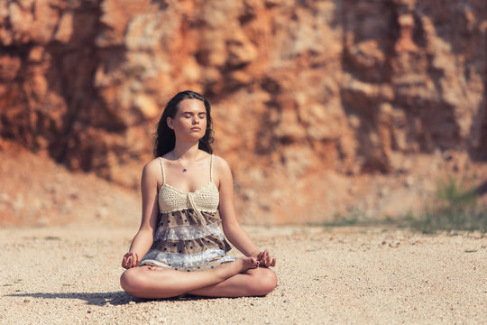 Young woman meditating outdoor in lotus position with eyes closed