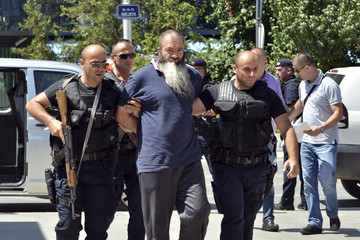 Kosovo police officers escort a man suspected of having fought with Islamist insurgents in Syria and Iraq as they arrive at a court in Pristina